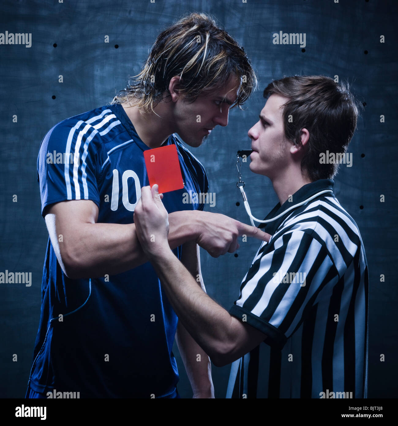 Studio shot of referee showing red card - Stock Image