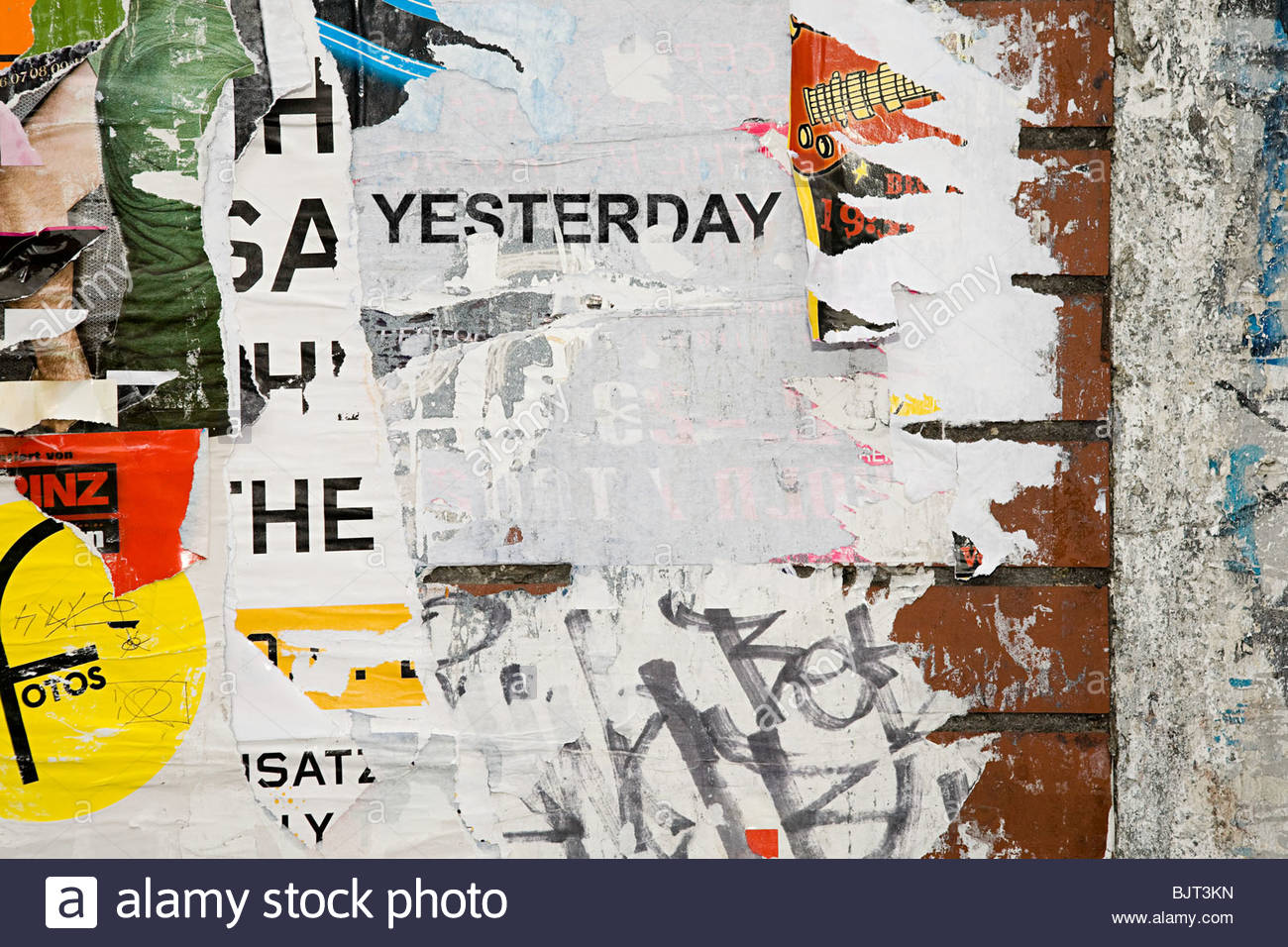Torn posters on a wall - Stock Image