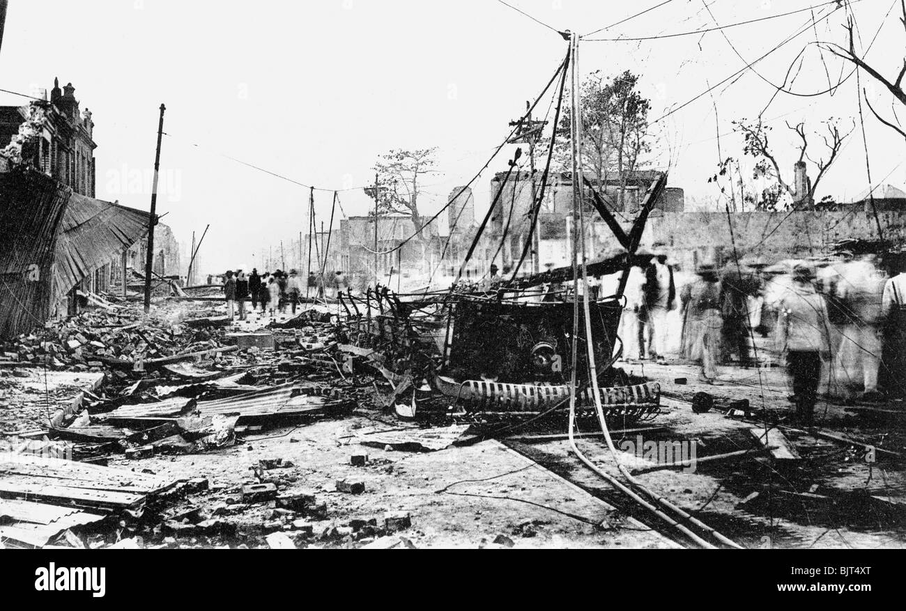 Earthquake damage and a burnt car, King Street, Kingston, Jamaica, 1907. Artist: Unknown - Stock Image