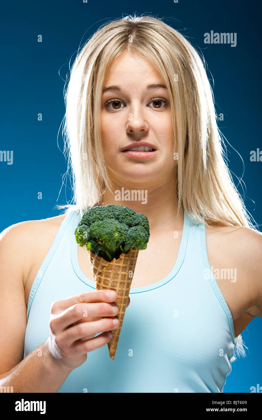 Studio portrait of young woman holding broccoli ice cream - Stock Image