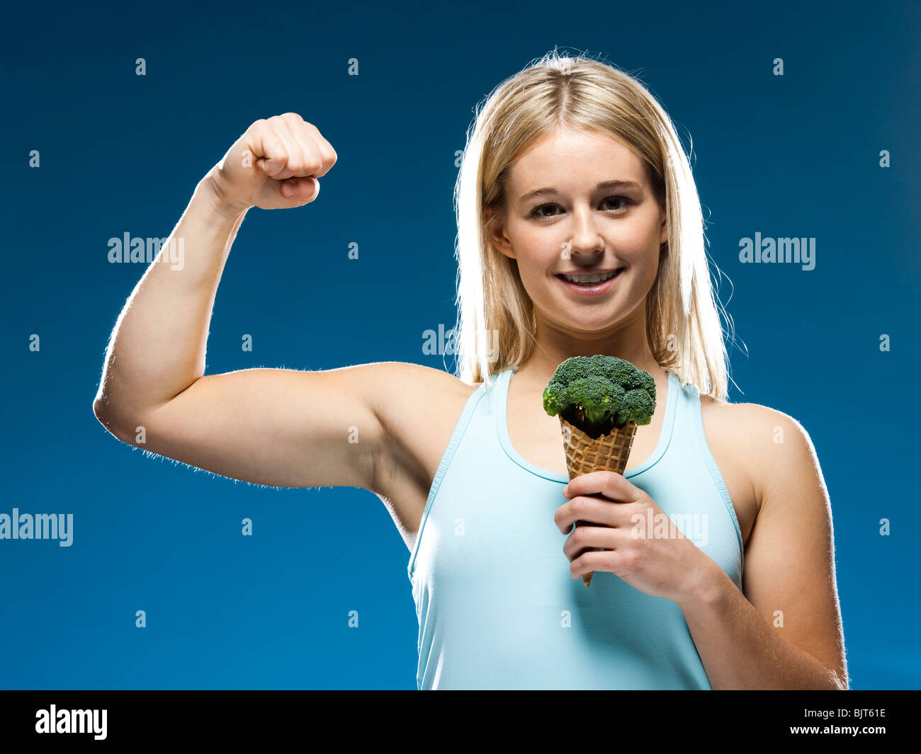 Studio portrait of young woman holding broccoli ice cream - Stock Image