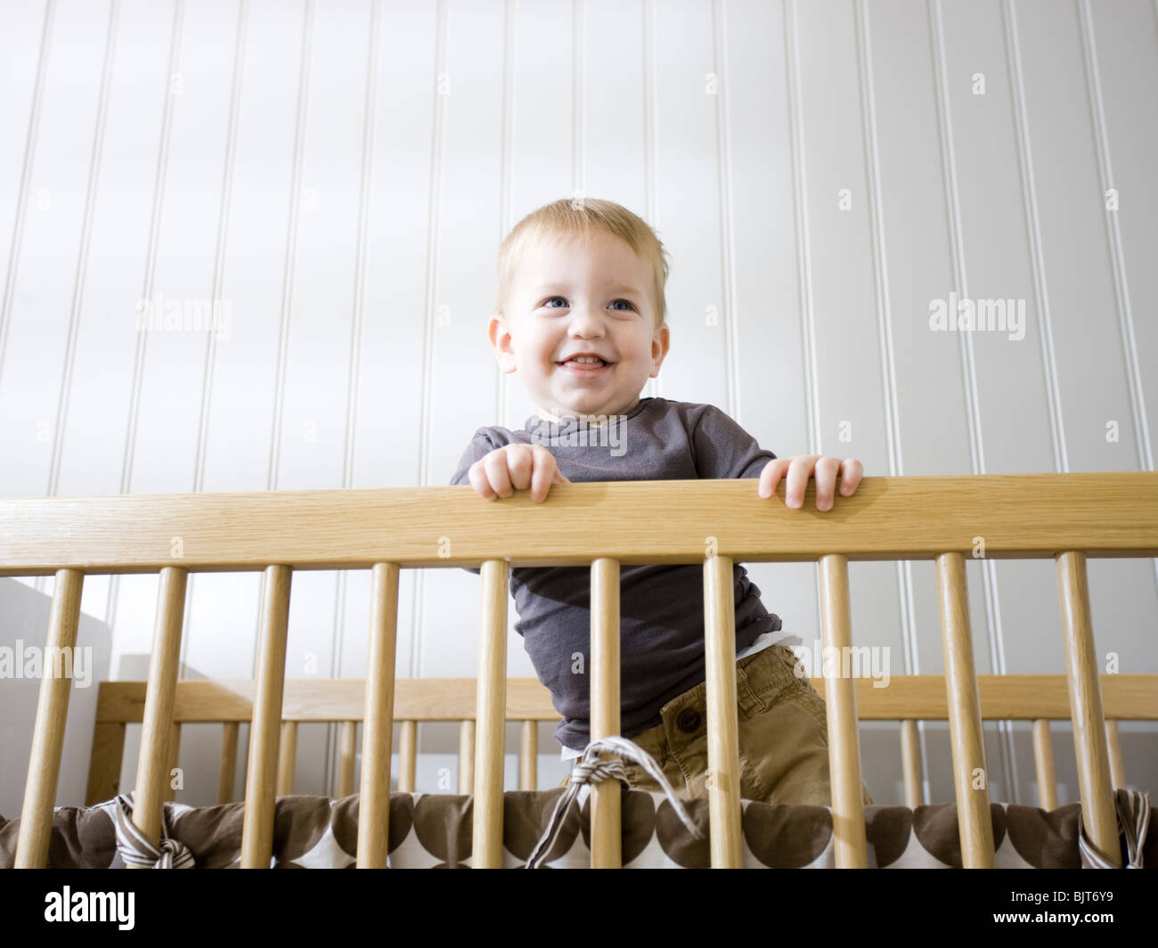 USA, Utah, Provo, Baby boy (18-23 months) standing in crib - Stock Image