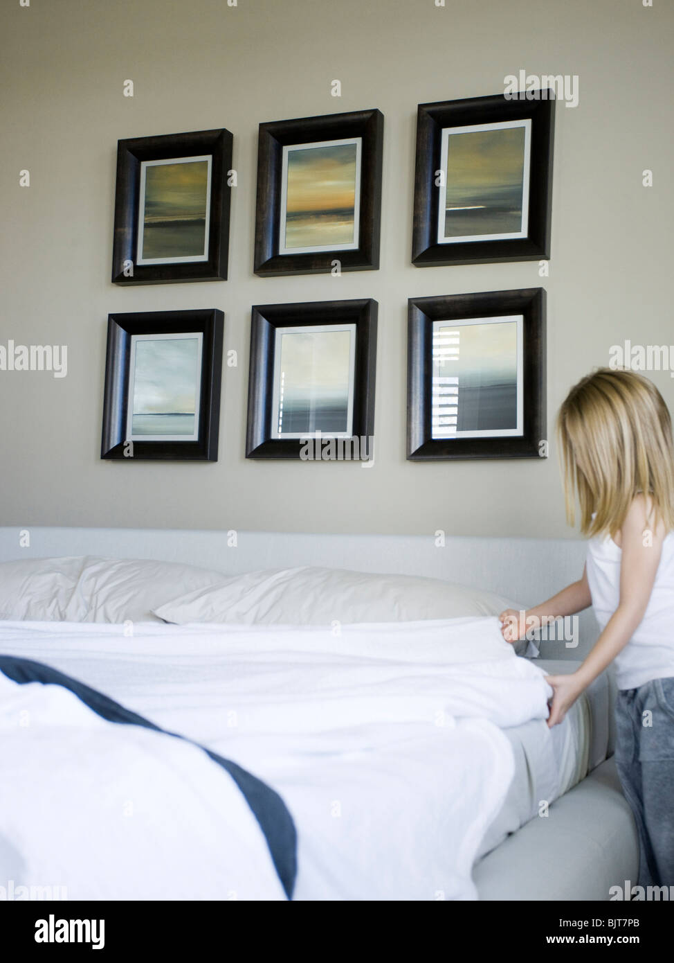 USA, Utah, Provo, Girl (4-5) making bed - Stock Image