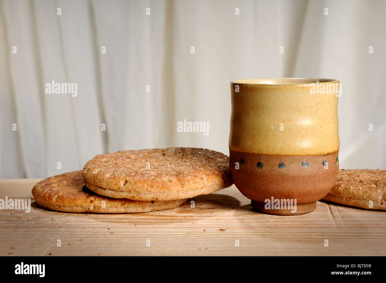 Bread and cup of wine, symbols of communion on wooden table - Stock Image