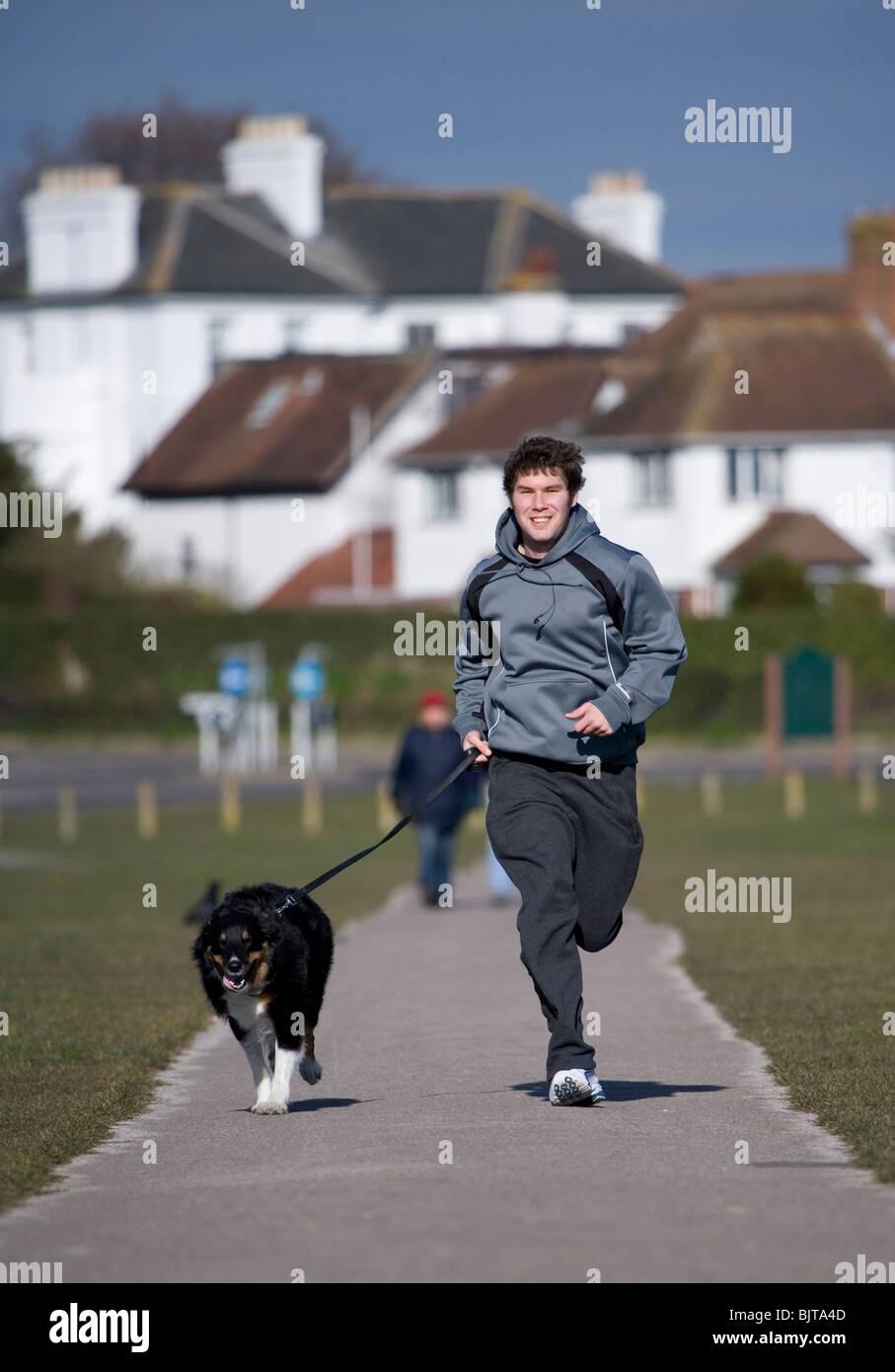 Recreation Adult male dog running with owner Gosport, UK - Stock Image