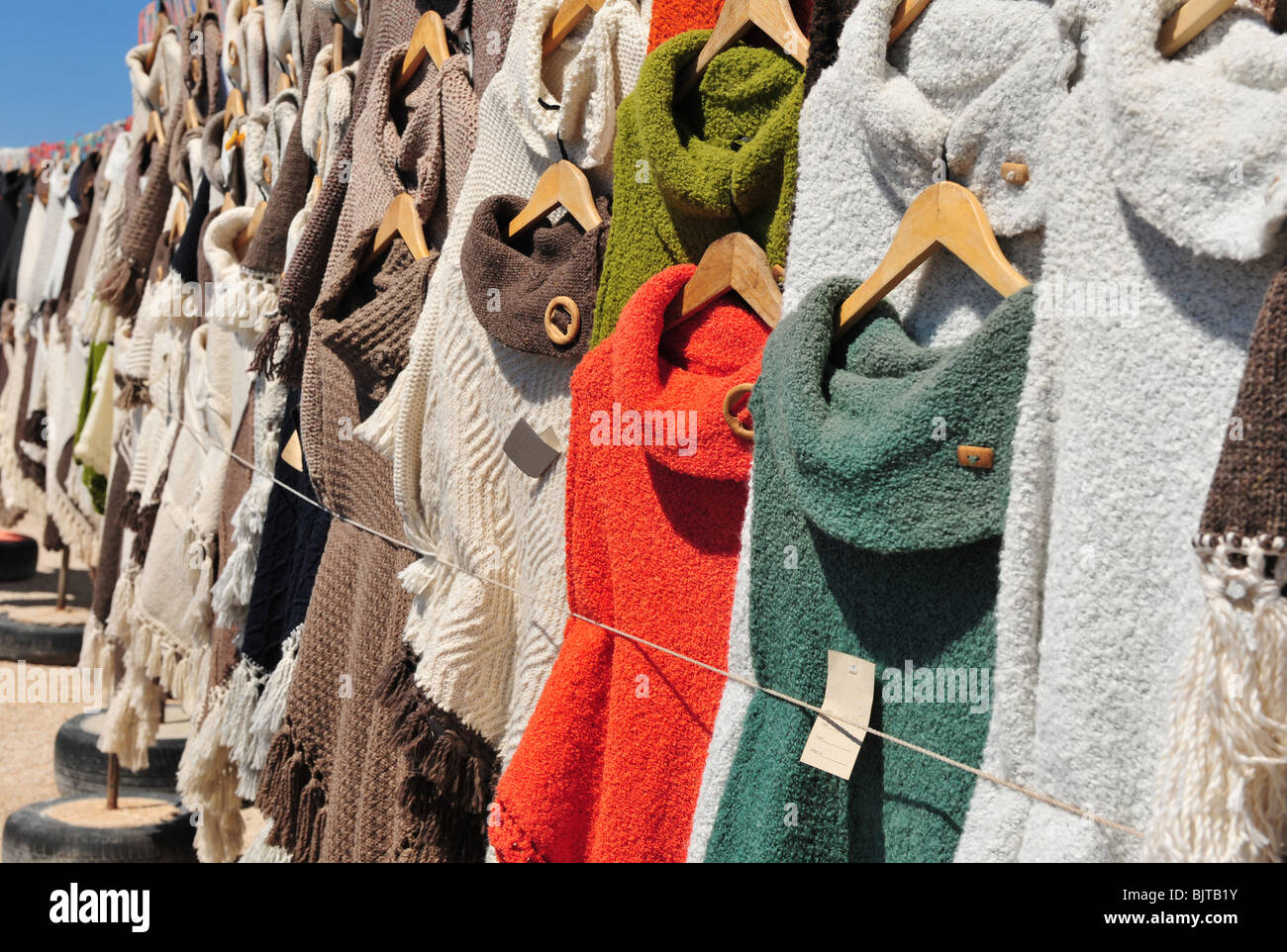 Poncho's and knitted garments for sale at a street market in Portugal, Algarve. Image taken at the stalls set - Stock Image