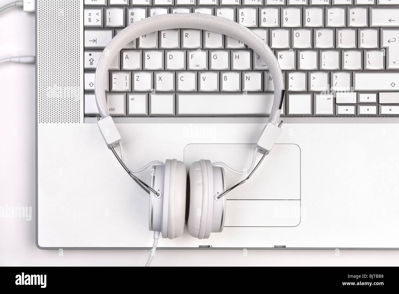 White elegance headphones on silver laptop keyboard. Top view. - Stock Image