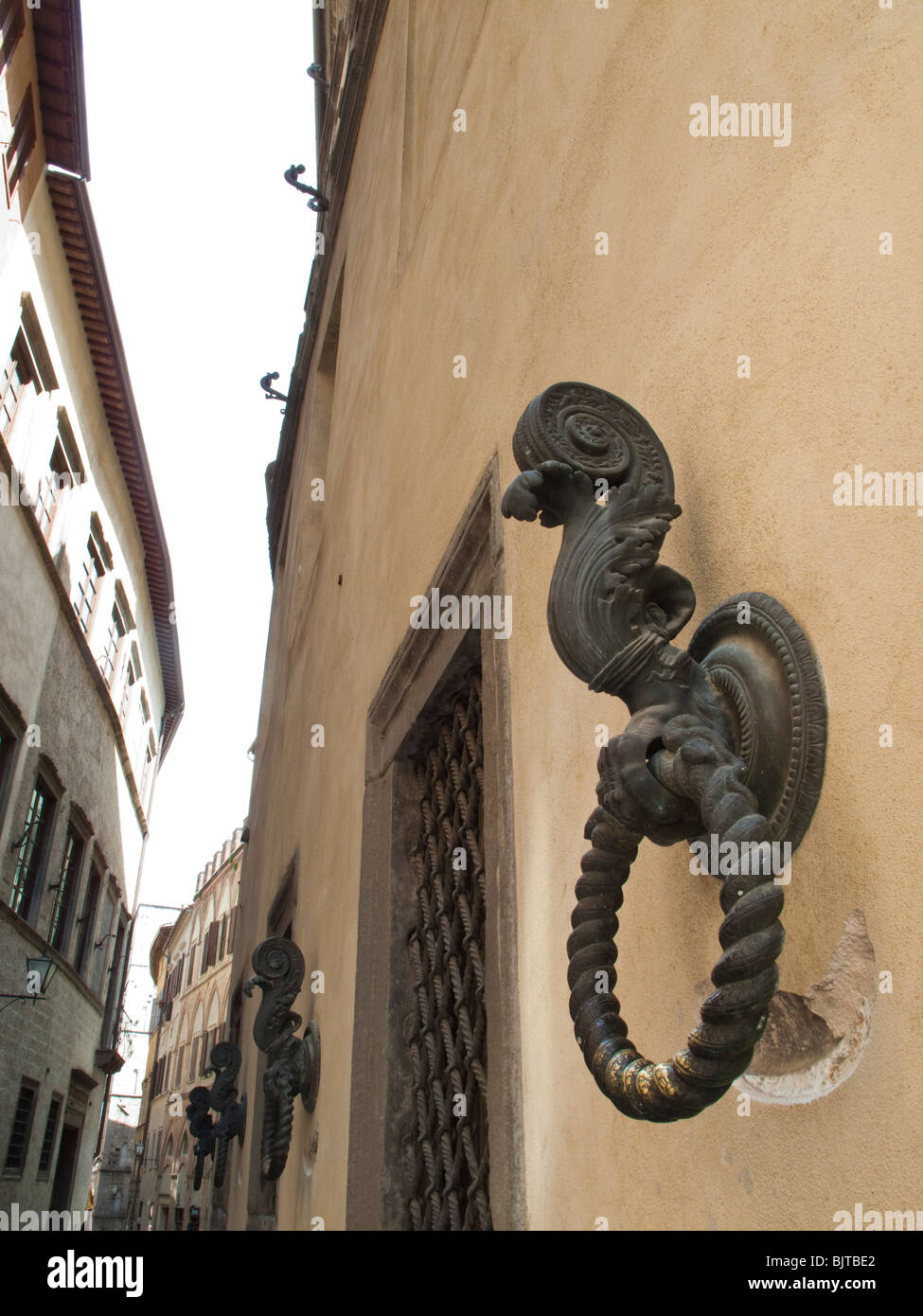 Line of 'Rein rings' on wall in Siena, Italy - Stock Image
