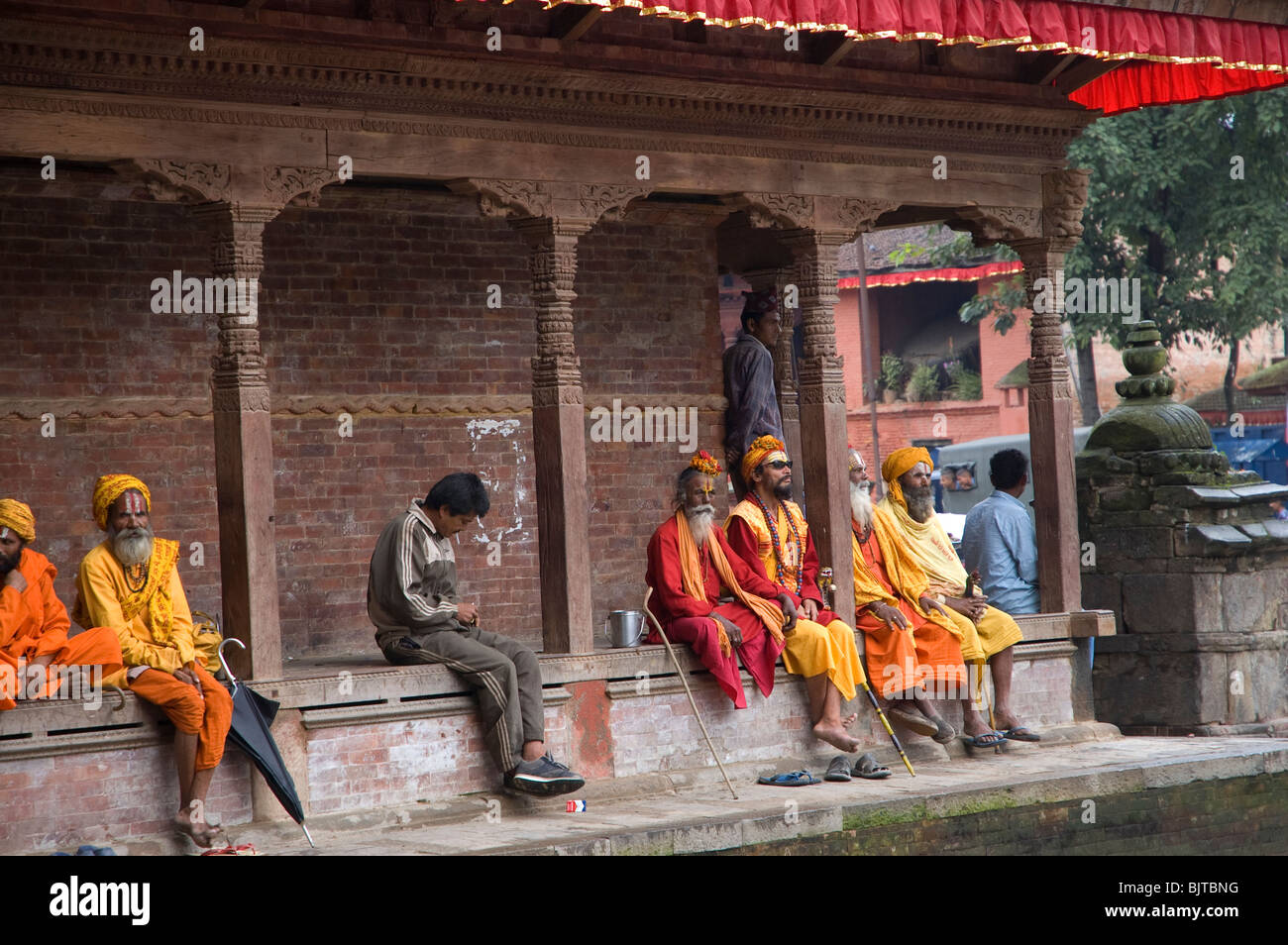 Sadus or holy men sit outside a temple in Durbar Square, Kathmandu, Nepal. - Stock Image