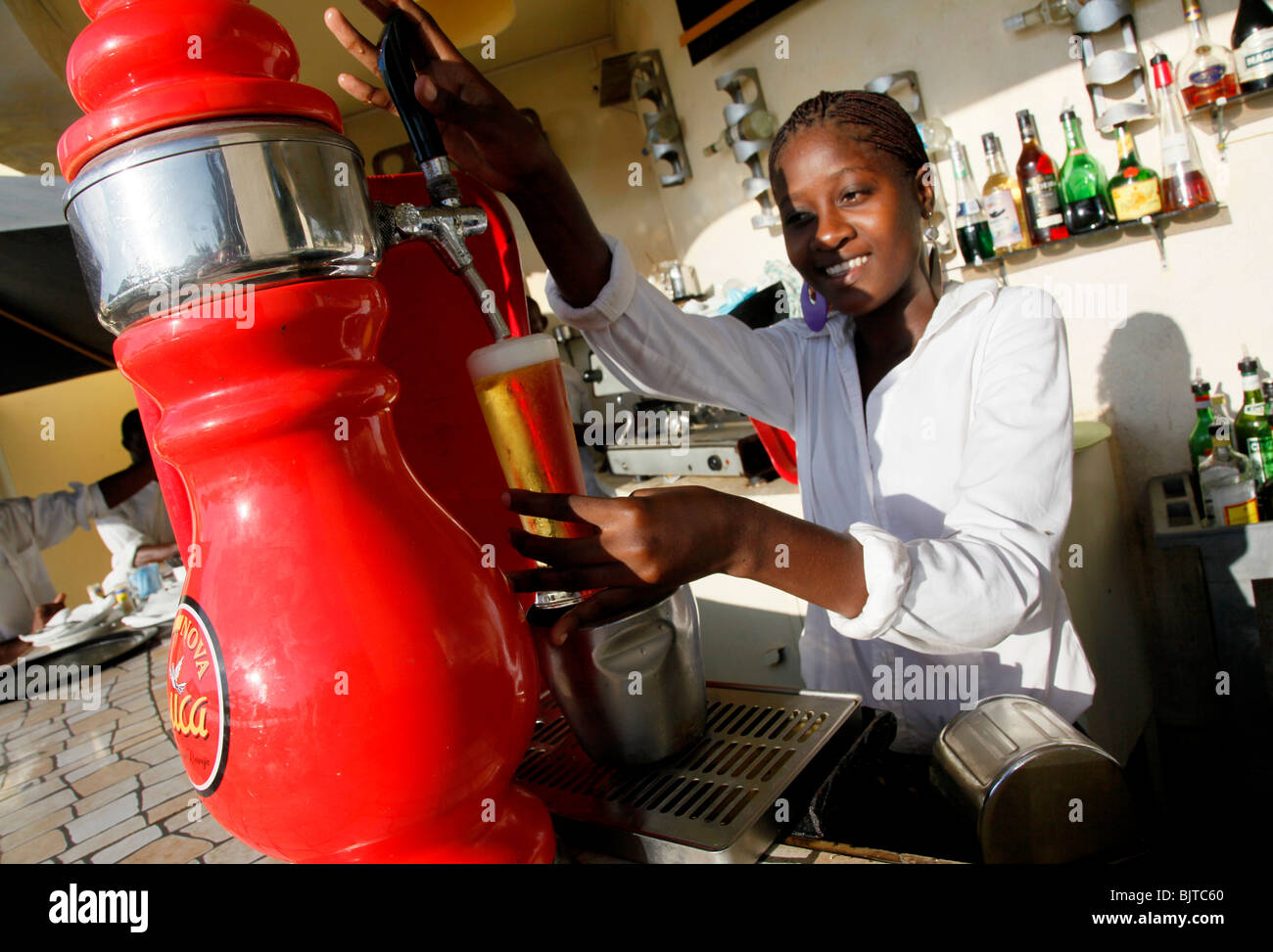 An Angolan waitress pours a draft beer from the bar. Benguela, Angola. Africa.  © Zute Lightfoot - Stock Image