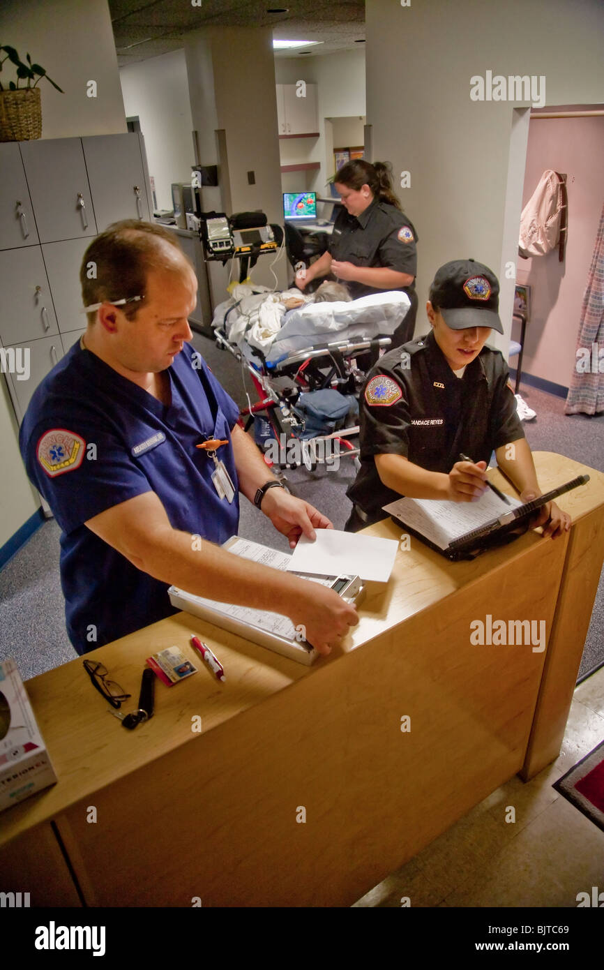 Emergency medical technicians, registered nurse (left), fill out paperwork after bringing a patient to a radiology - Stock Image