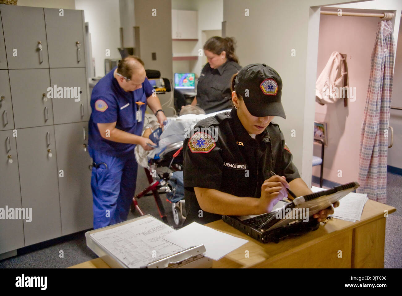 Emergency medical technicians, one of them a registered nurse (background, left), fill out paperwork at  radiology - Stock Image