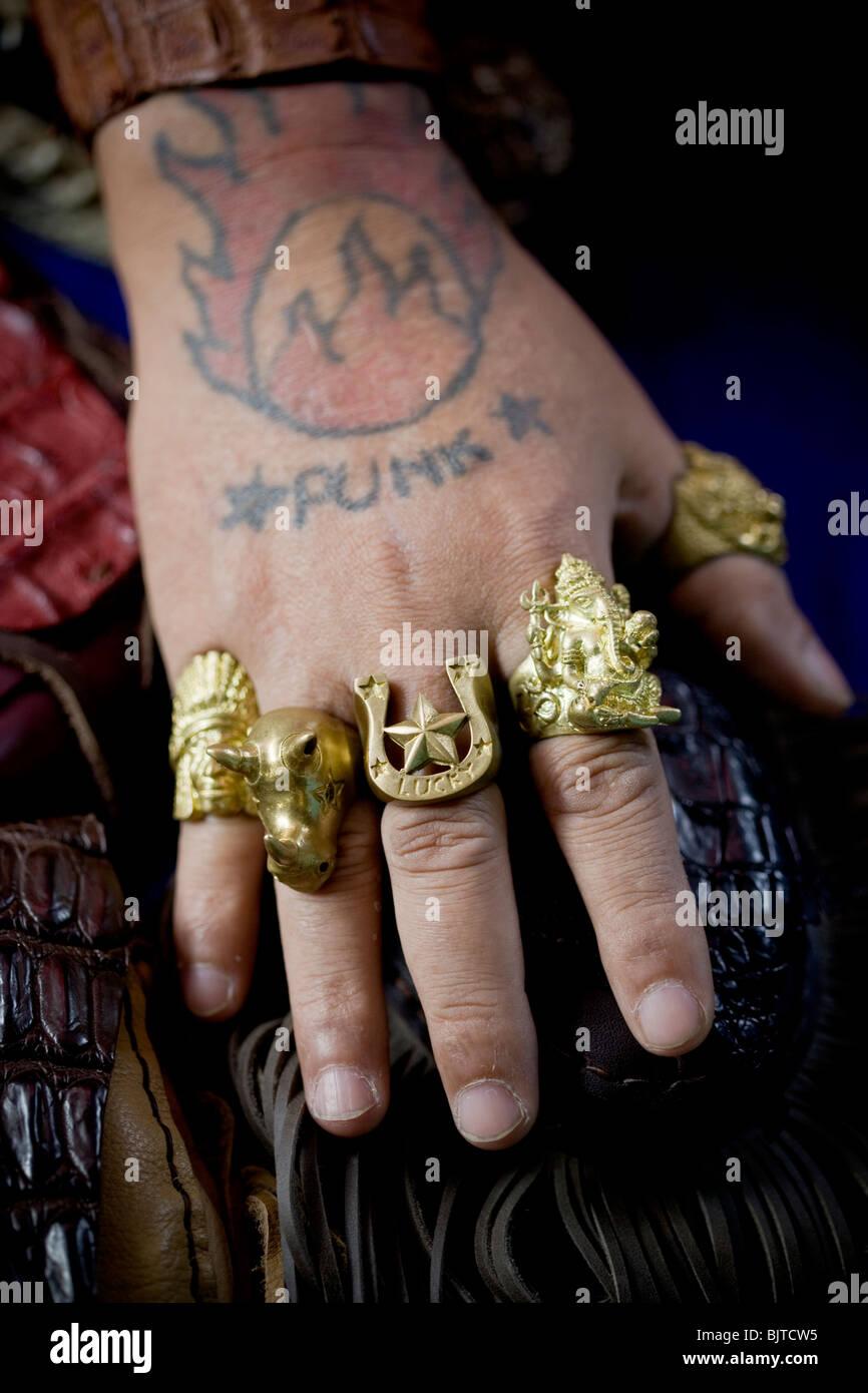 Punk Tattoo and Rings on the hand of Man at  Chatuchak Market Bangkok Thailand Stock Photo