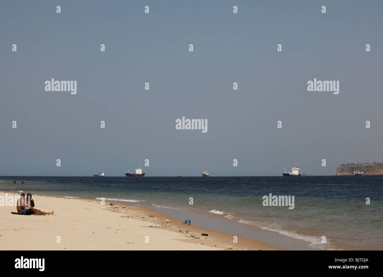 Ships and tankers waiting to dock at the port. As seen from the beach at the end of The Ilha. Luanda. Angola. Africa. - Stock Image