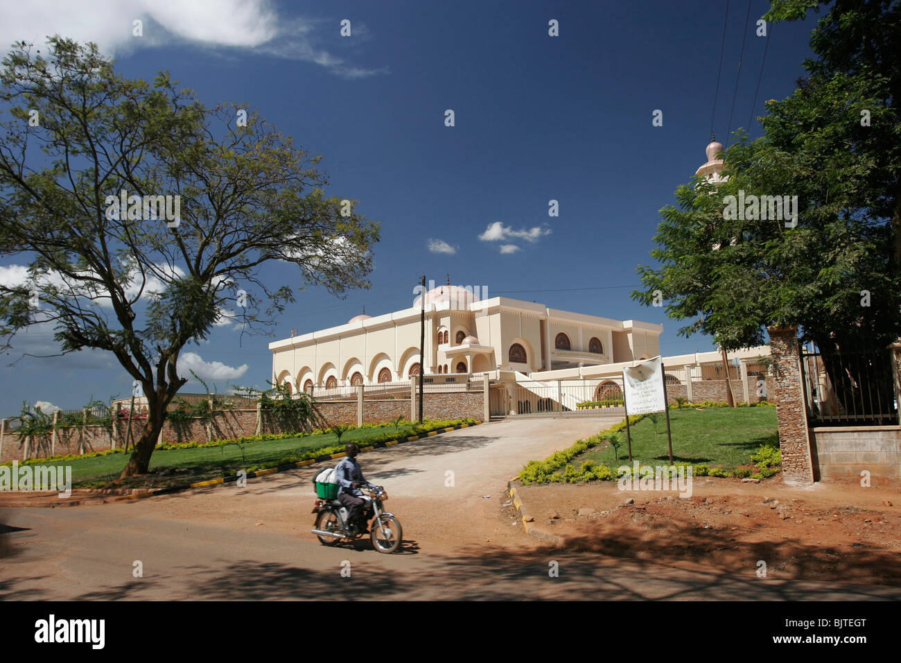 Motorcyclist drives past the colonel Gaddafi mosque. Kampala. Uganda. Africa - Stock Image