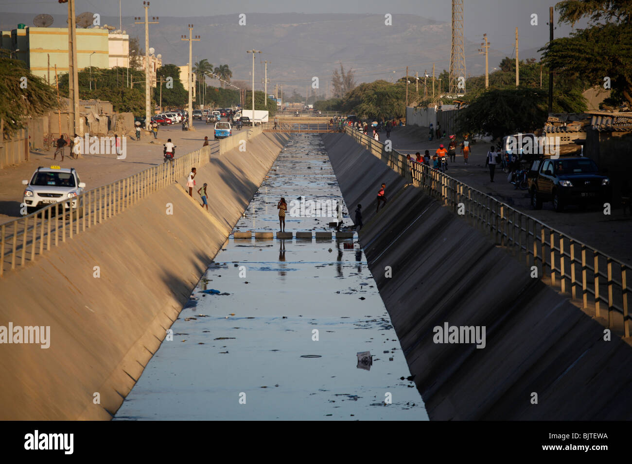 Crossing the storm drain and sewer that divides the wealthy area of Benguela from the poorer barrios.Benguela city. - Stock Image