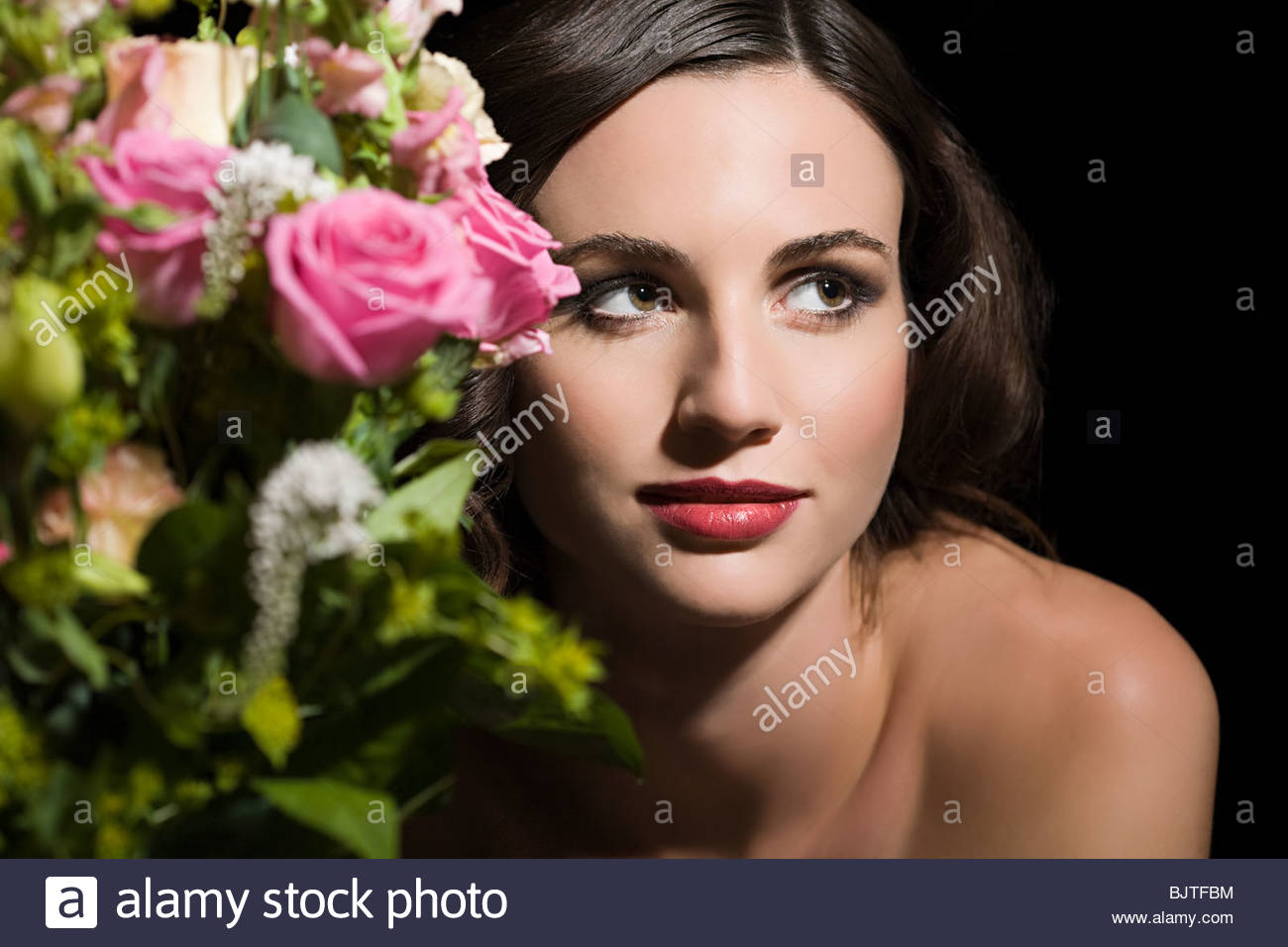 Woman behind a bunch of flowers - Stock Image