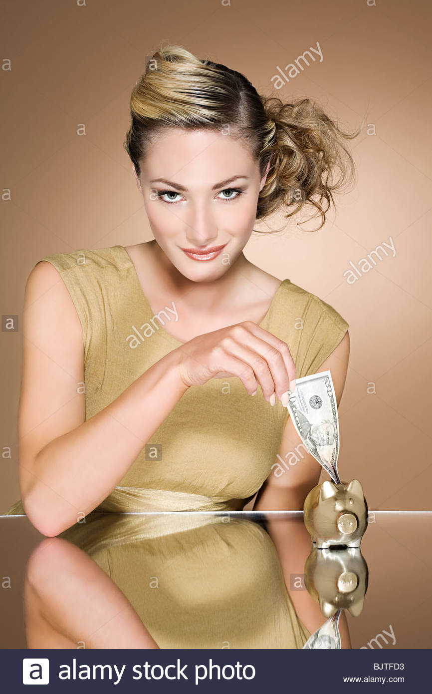 Woman putting cash in a piggy bank - Stock Image