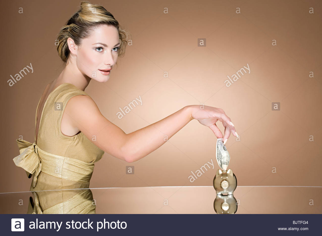 Woman putting cash in piggy bank - Stock Image
