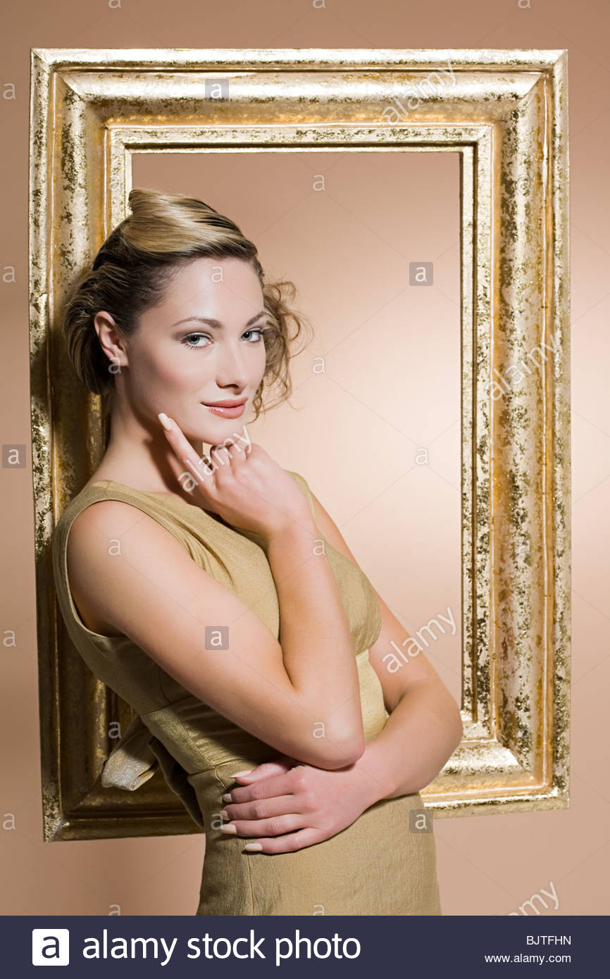 Woman standing by a golden picture frame - Stock Image