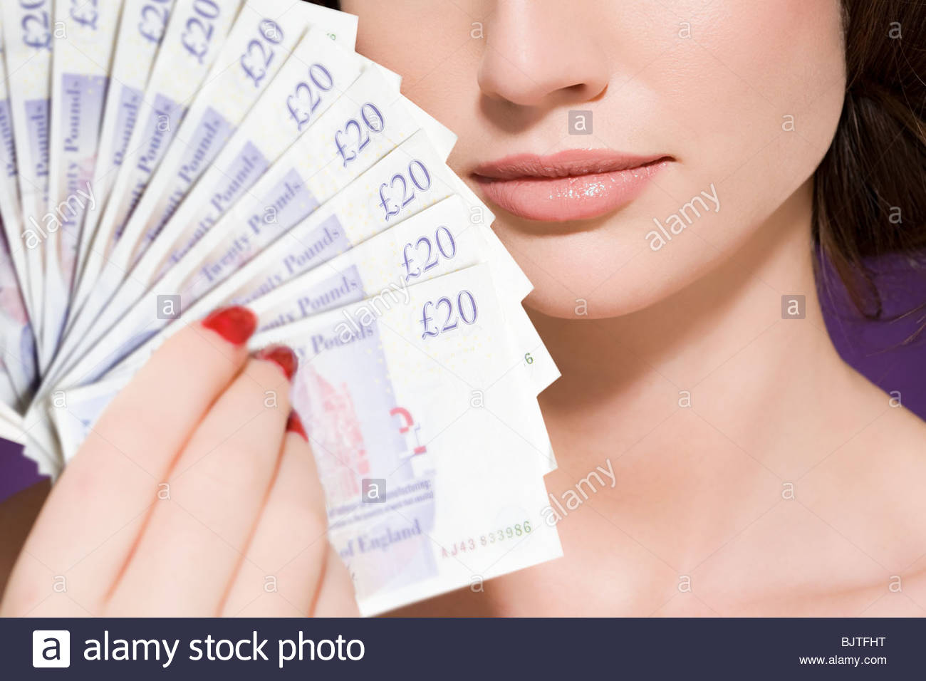 Woman holding banknotes - Stock Image