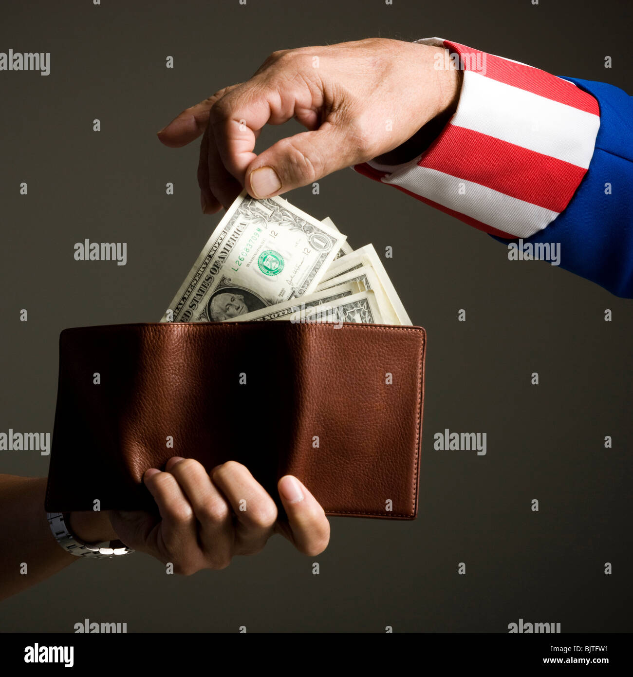 Man in Uncle Sam's costume taking money from wallet, studio shot - Stock Image