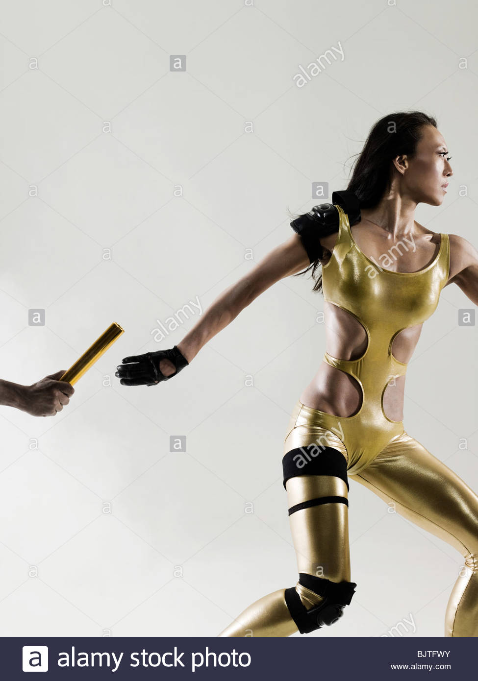 Runners passing a relay baton - Stock Image