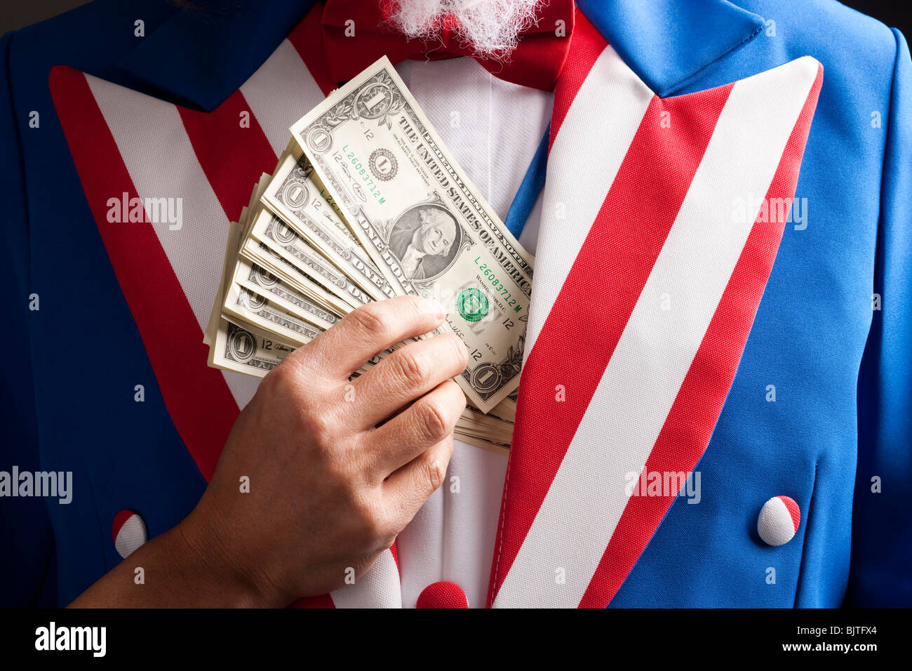 Hand hiding banknotes under vest, studio shot - Stock Image