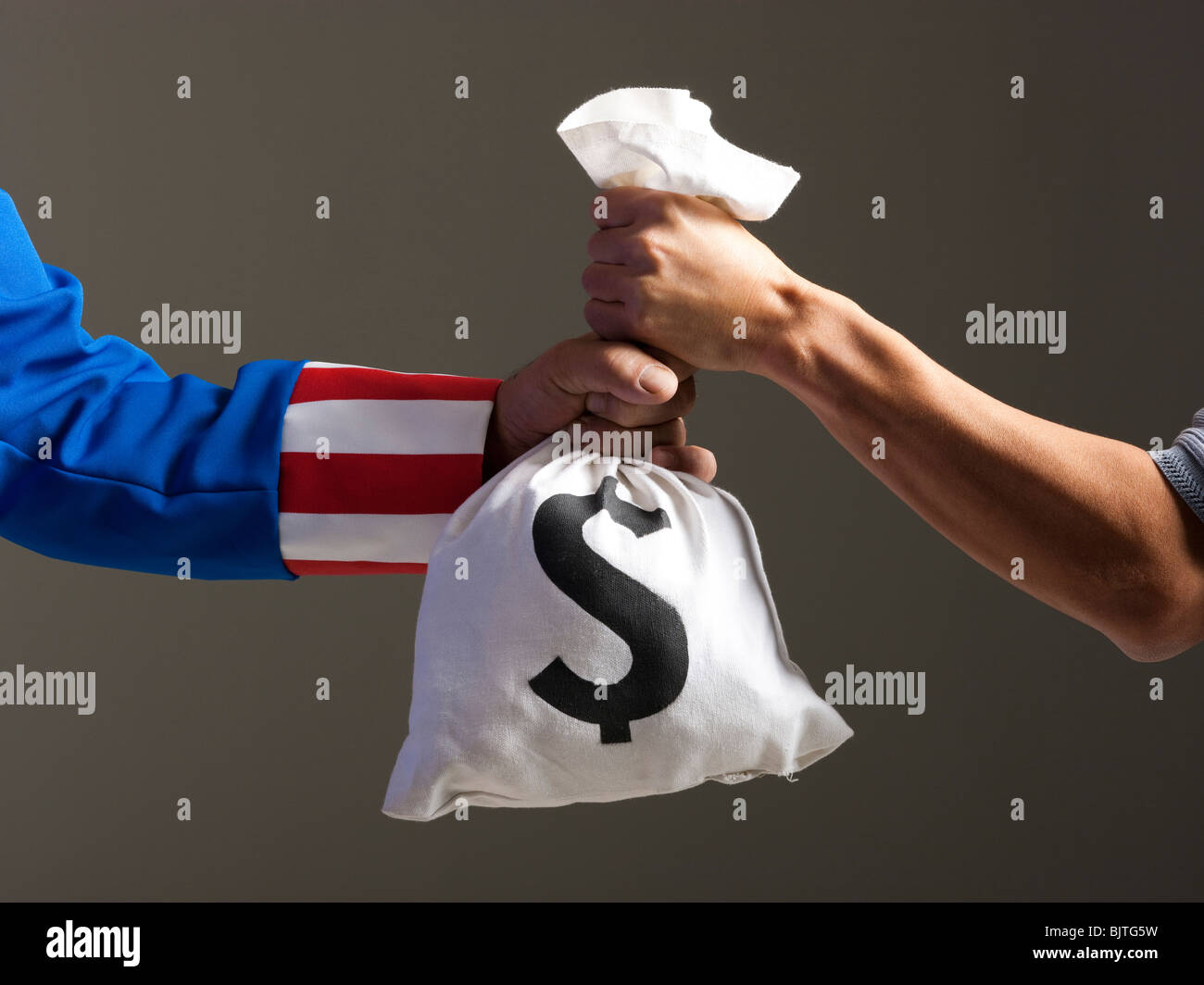 Two men holding bag with money, studio shot - Stock Image