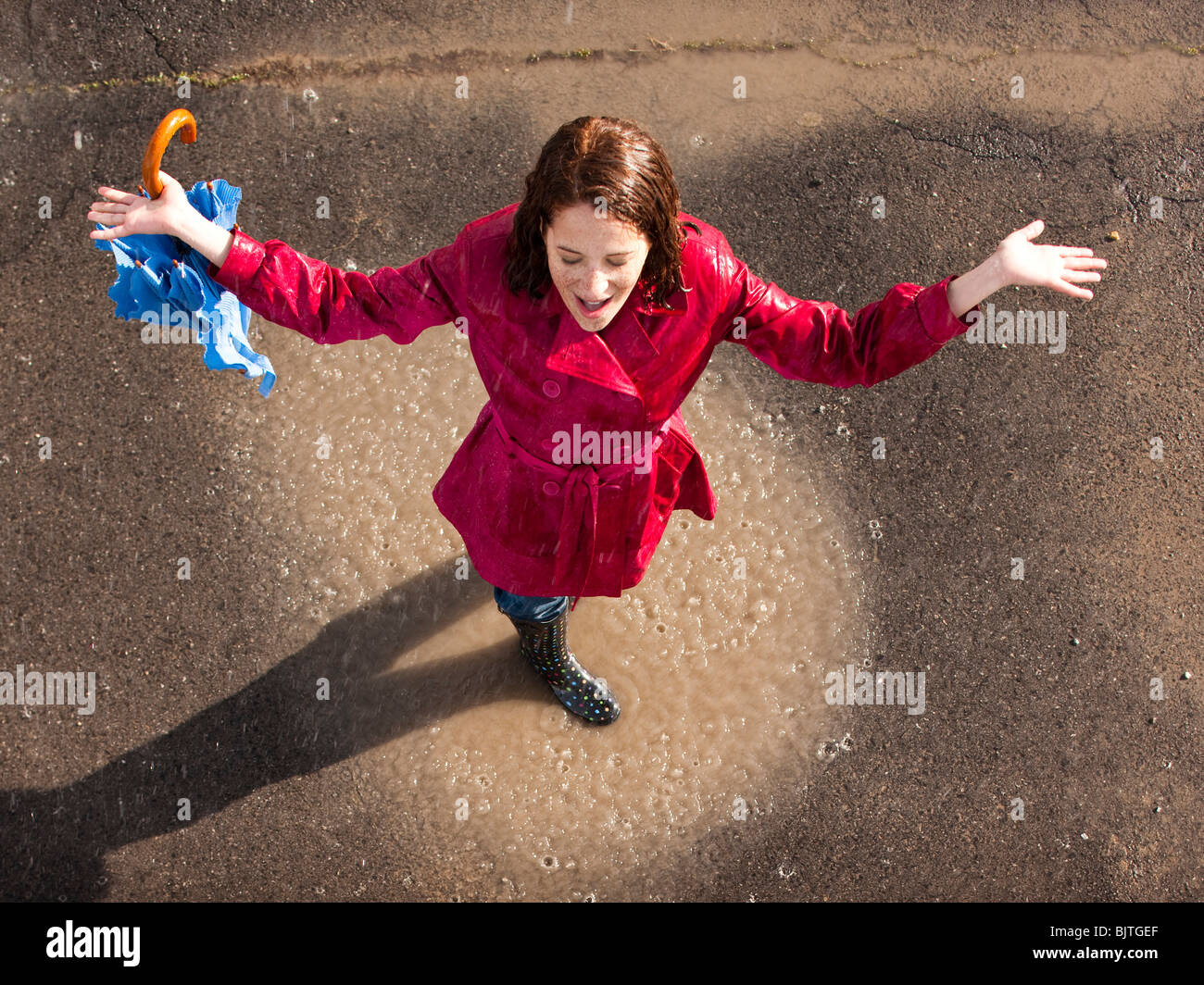 Young woman standing in rain with arms outstretched - Stock Image