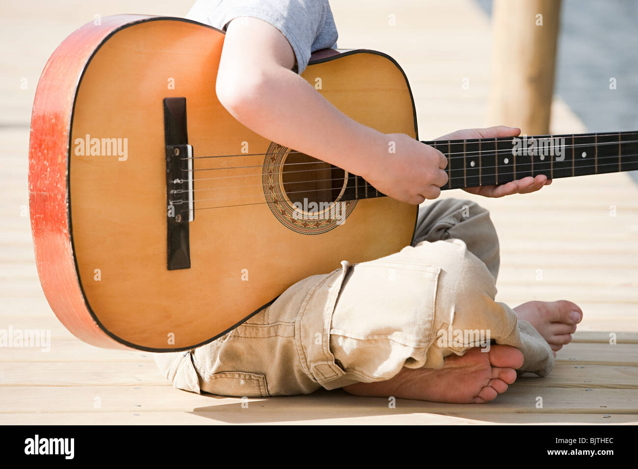 Boy playing guitar - Stock Image