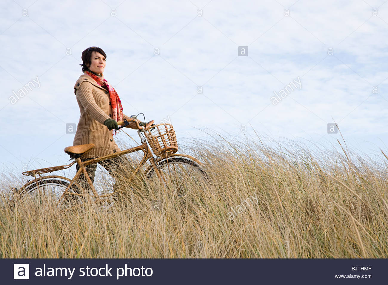 Woman in field with bicycle - Stock Image