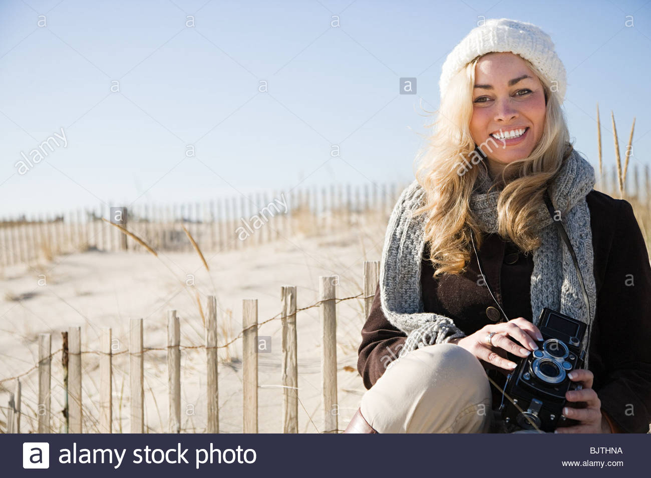 Woman at beach with camera Stock Photo