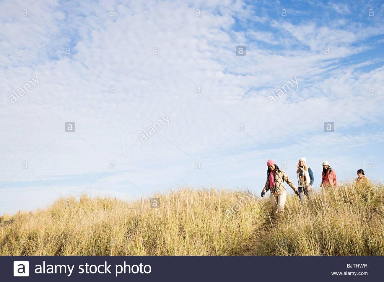 Female friends walking in marram grass - Stock Image