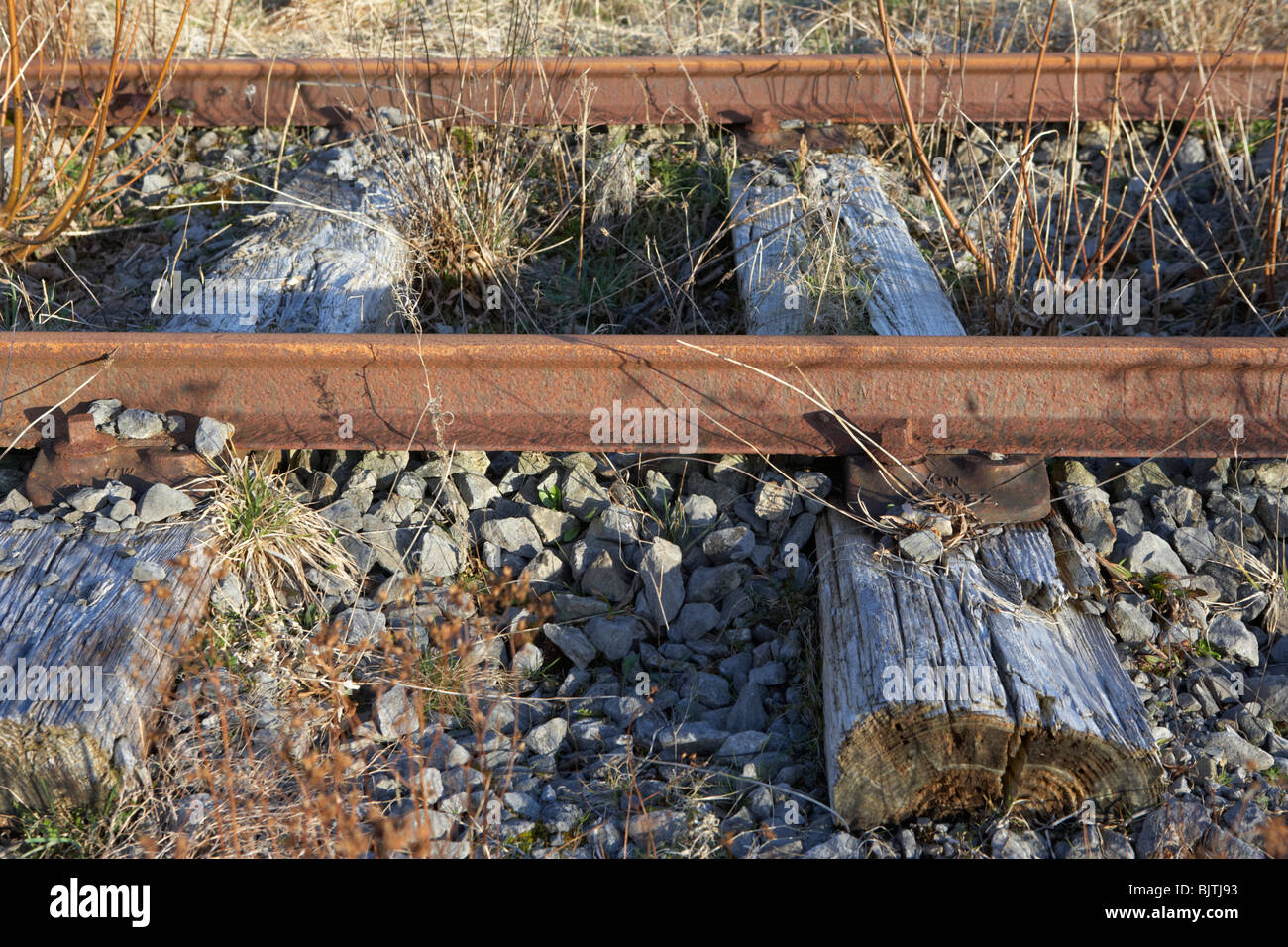 old abandoned great southern and western railway line connected to worn wooden sleepers in county sligo republic - Stock Image