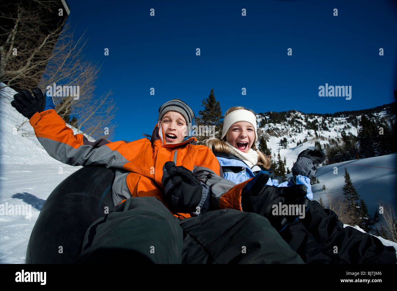 Brother And Sister Sliding On Inner Tube Stock Image