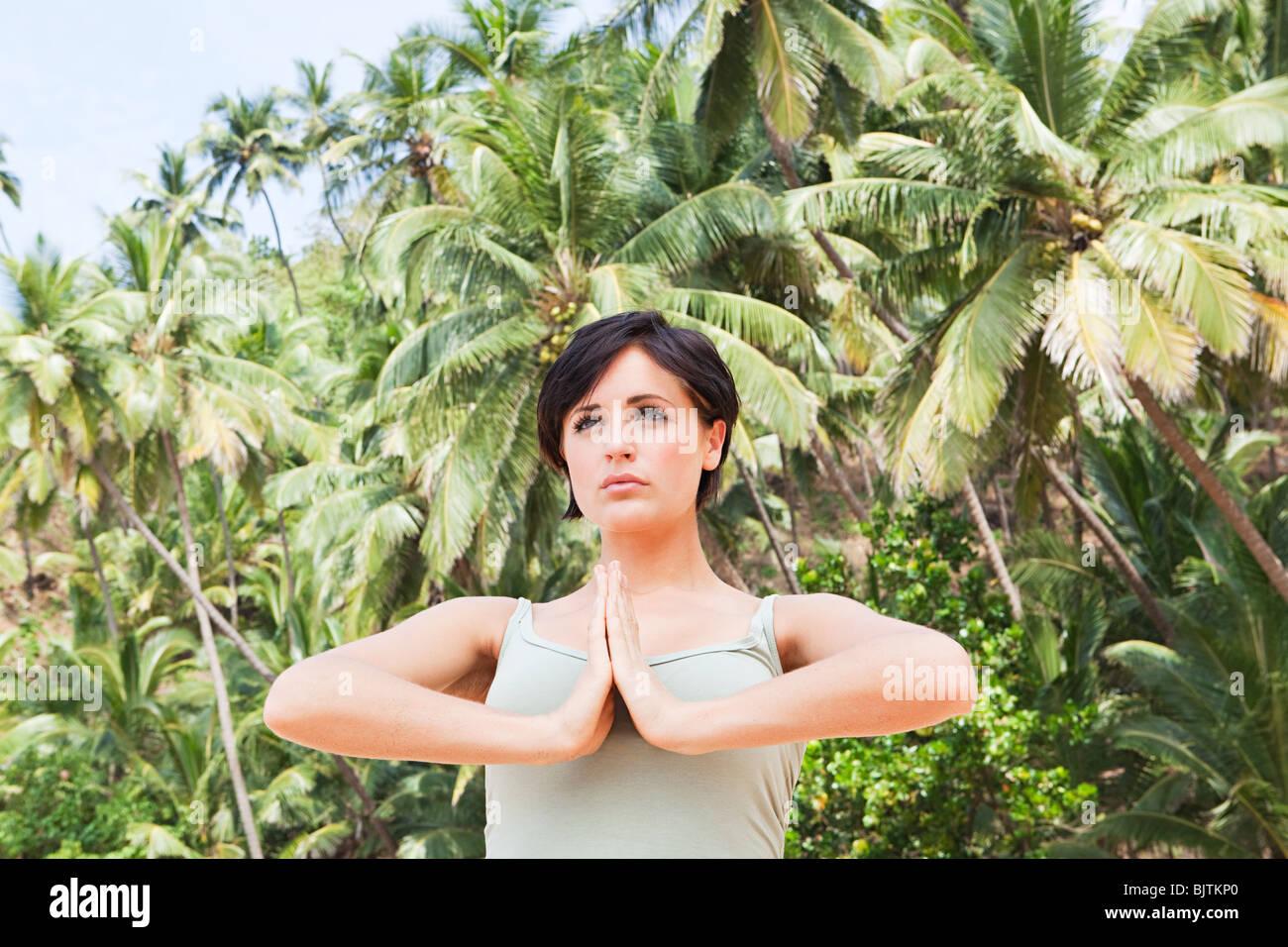 Woman in prayer pose - Stock Image