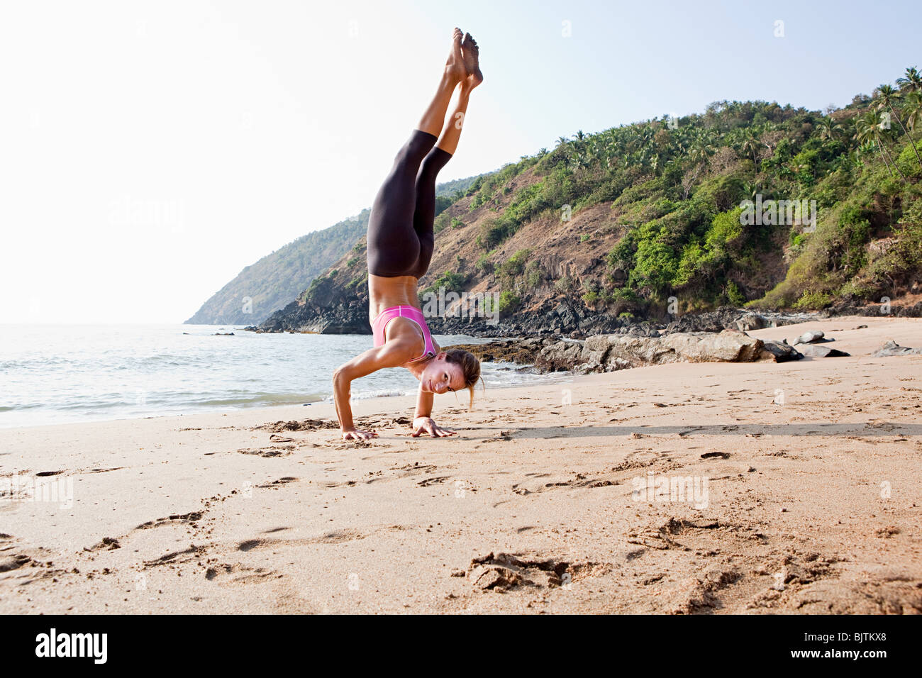 Woman doing handstand on beach - Stock Image