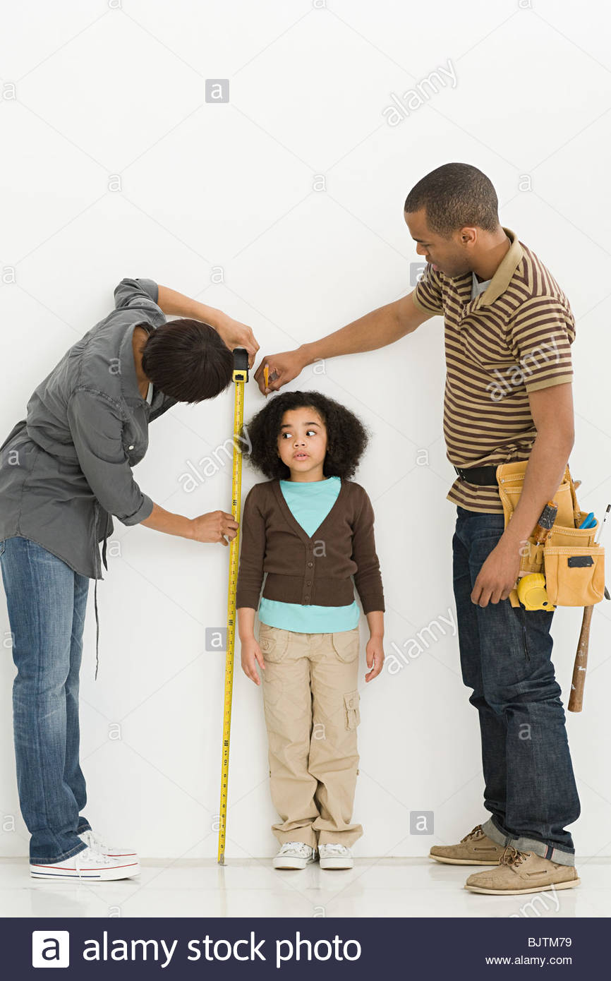 Parents measuring daughter - Stock Image