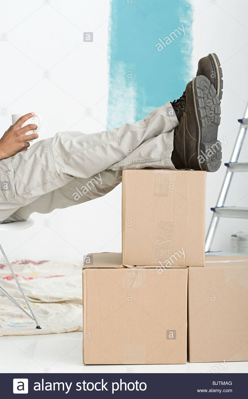 Decorator with feet on boxes - Stock Image