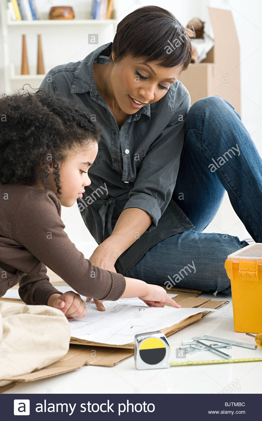 Girl and mother looking at instruction manual - Stock Image