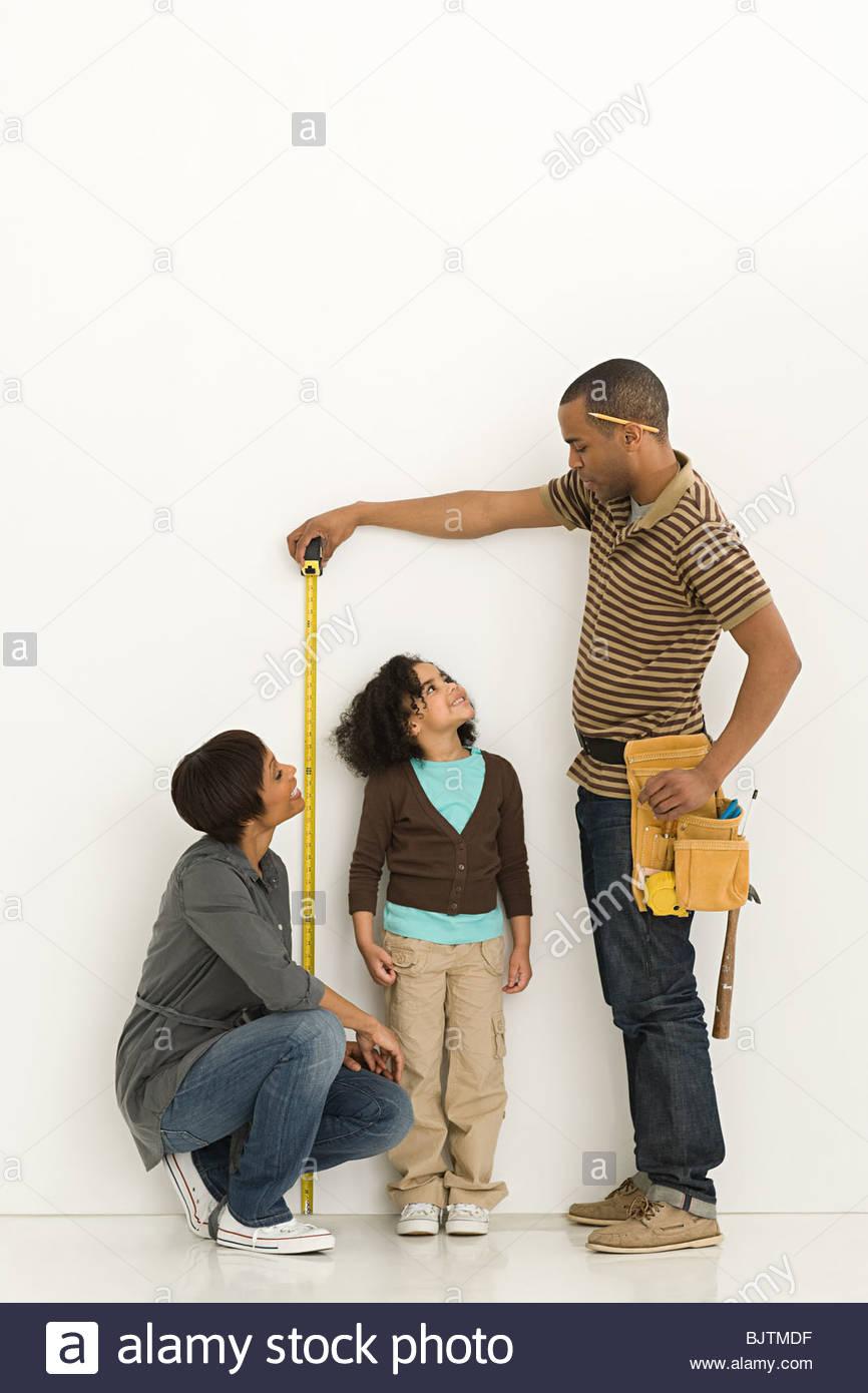 Parents measuring daughter - Stock Image