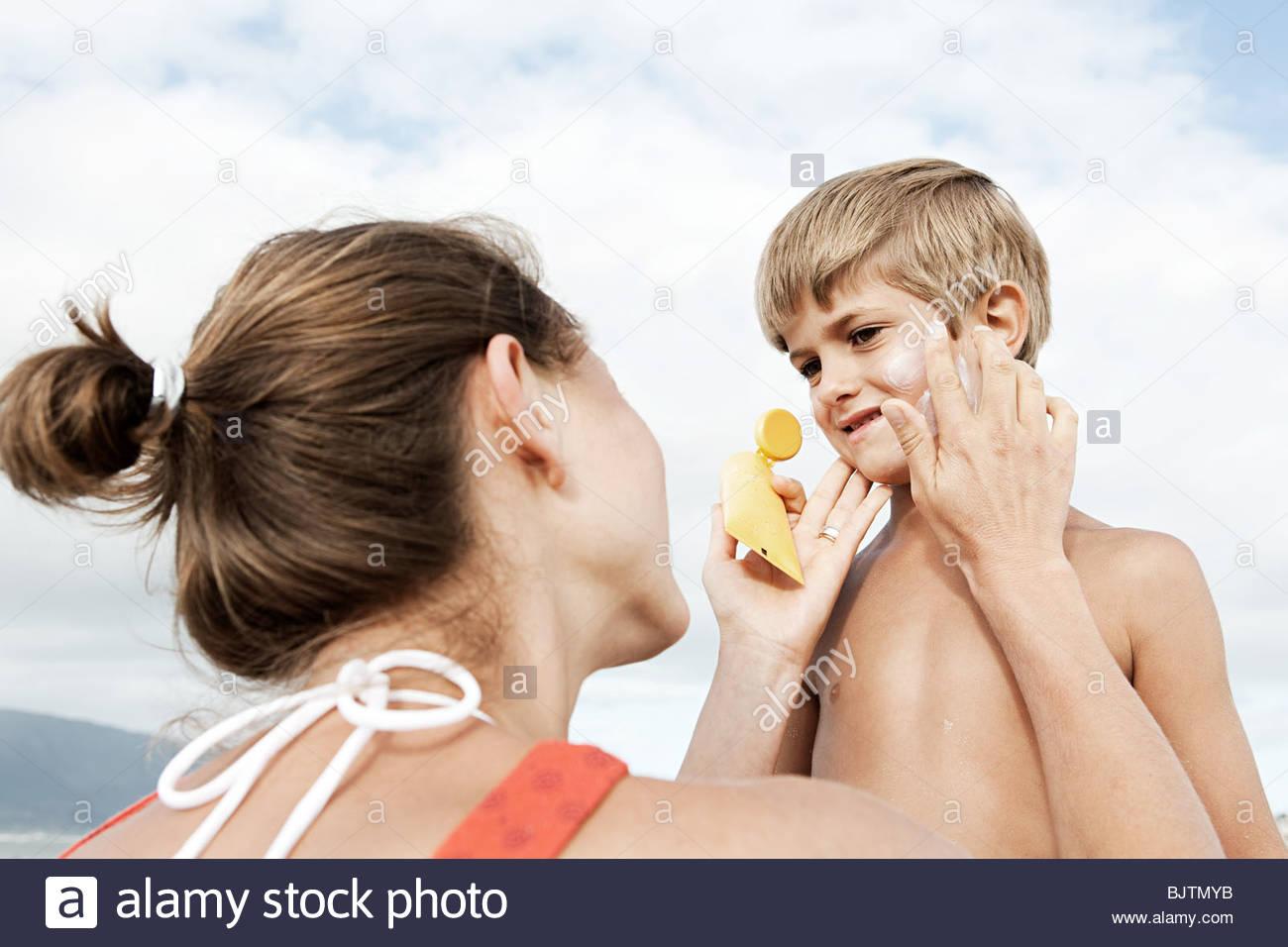 Mother applying suncream to son - Stock Image