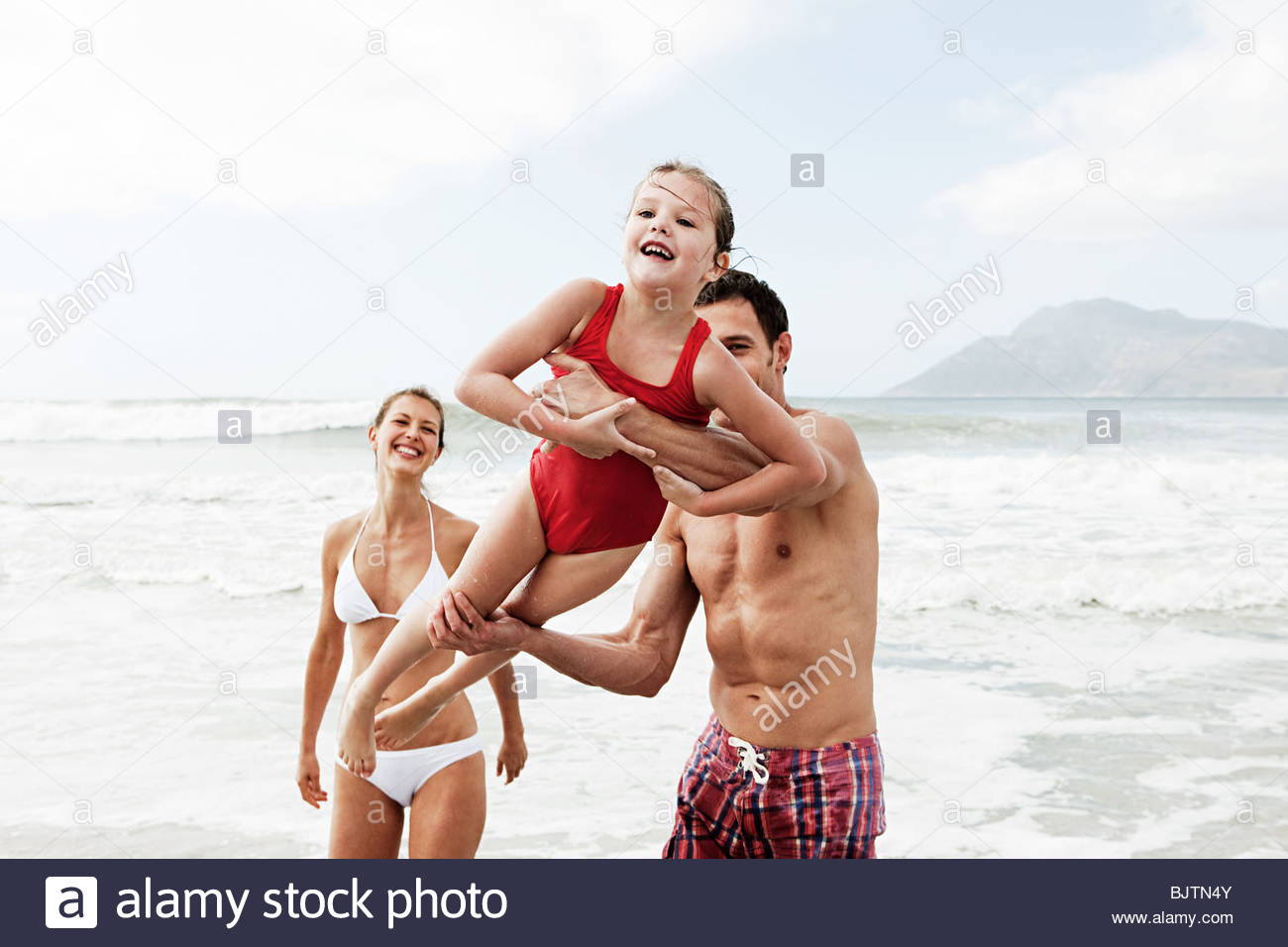 Girl and parents playing by sea - Stock Image