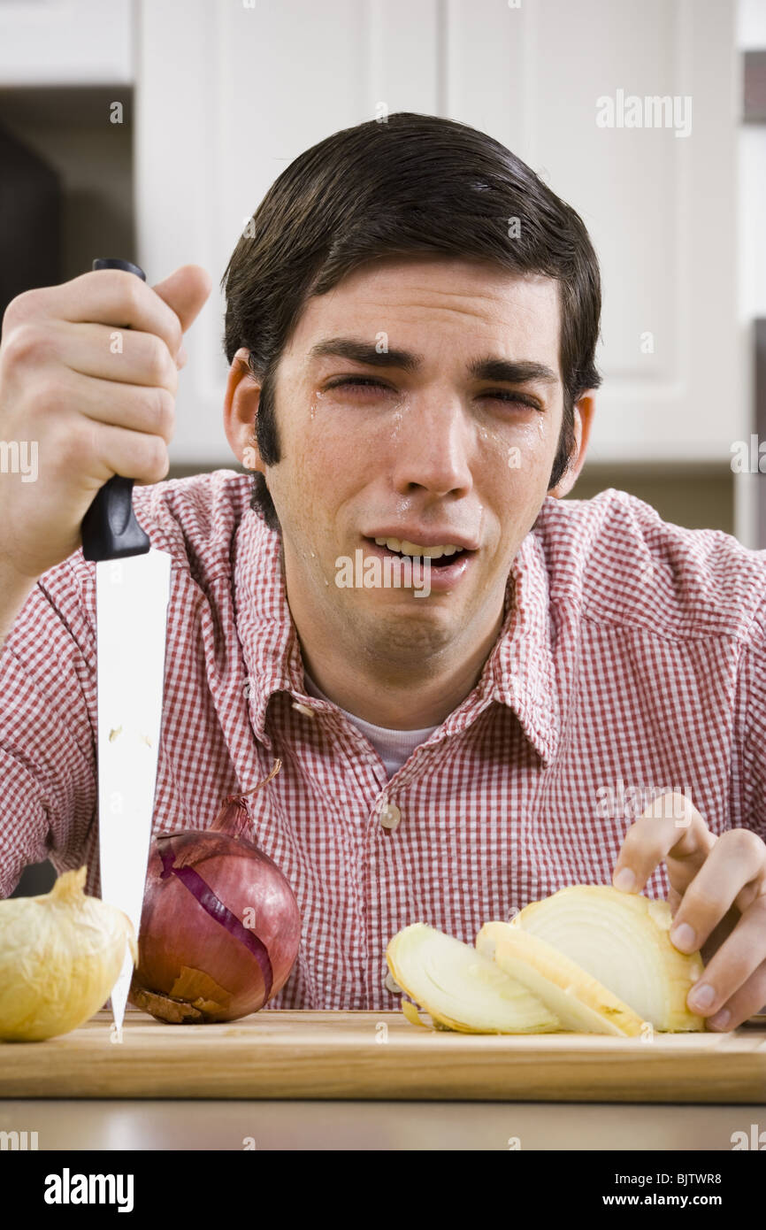 Man slicing onion and crying - Stock Image