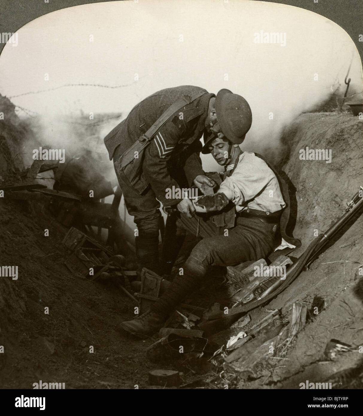 Soldier receiving first aid from a sergeant in a sap, Battle of Peronne, World War I, 1914-1918. - Stock Image