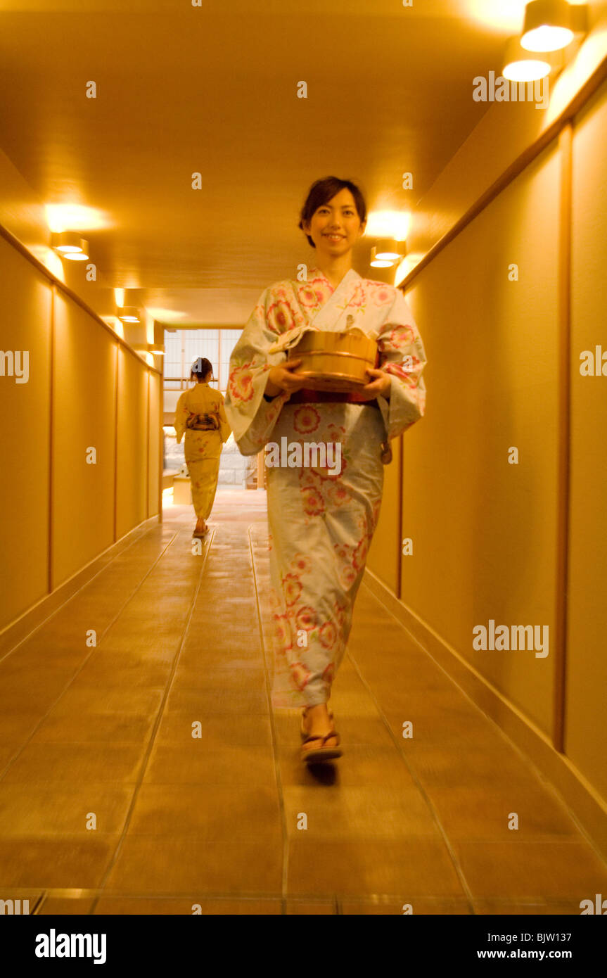 Two women wearing yukata walking through the corridor of a health spa Stock Photo