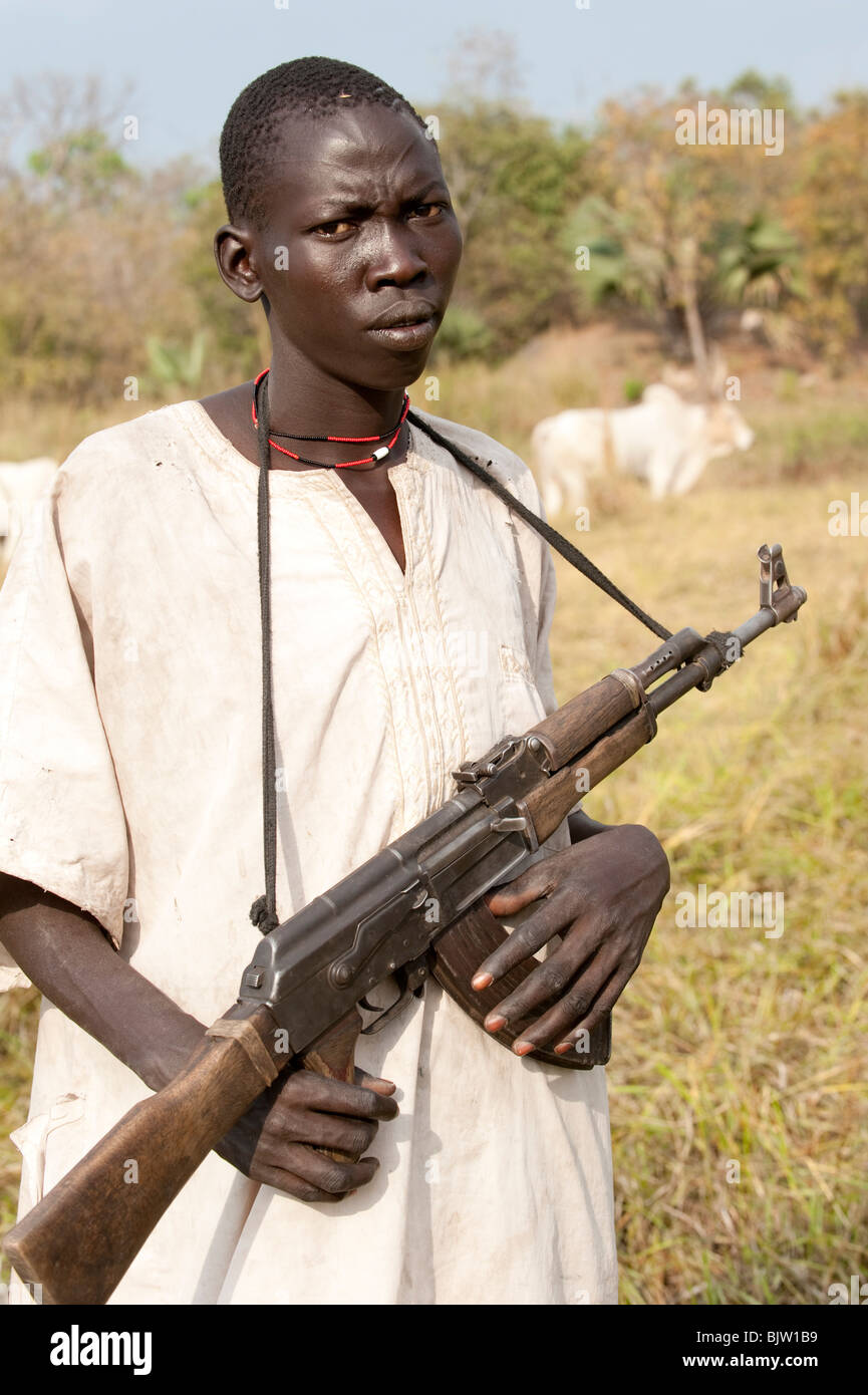 SOUTH-SUDAN, Cuibet near Rumbek , Dinka tribe, shepherd armed with Kalashnikov AK-47 protect their Zebu cows from - Stock Image