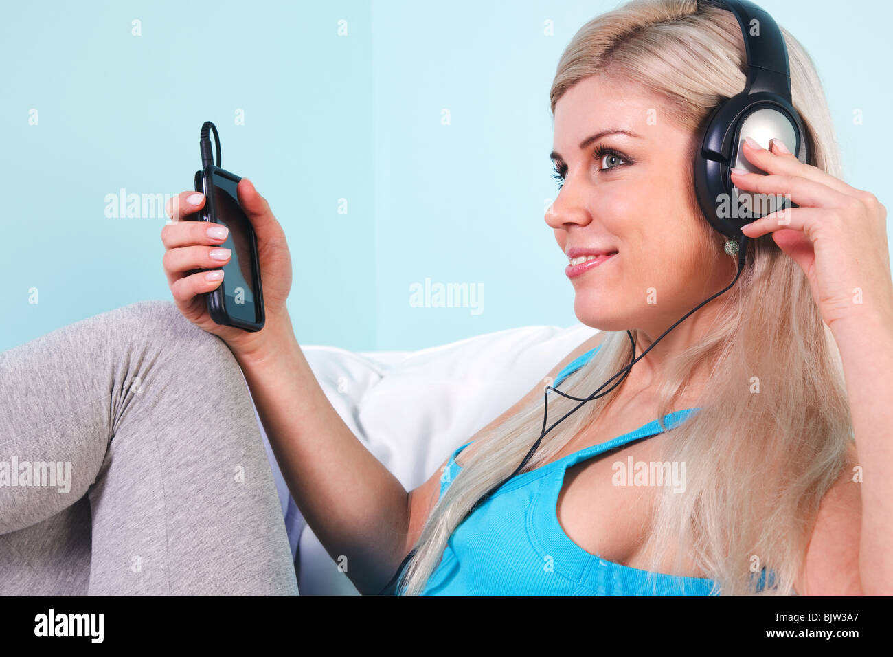 Young blond woman sat in an armchair listening to music on her mp3 player through headphones - Stock Image