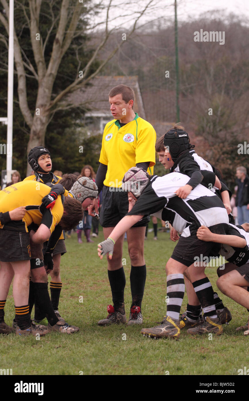 Referee with junior rugby young players in club competition match preparing to scrum scrummage down EDITORIAL USE - Stock Image